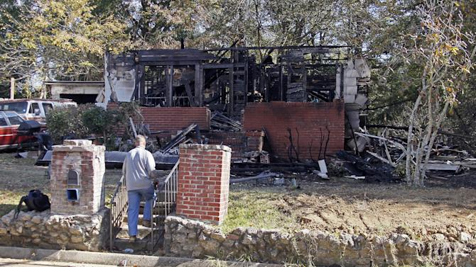 A Jackson, Miss., Fire Department investigator inspects the west Jackson, Miss., home Wednesday, Nov. 14, 2012, that local authorities said a small plane carrying three people crashed into Tuesday evening. The home's resident  escaped with non-life threatening injuries but authorities confirmed the plane's passengers were dead.  (AP Photo/Rogelio V. Solis)
