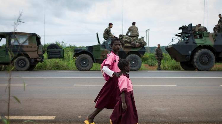 Children walk next to French troops along a road to the Central African Republic on December 5, 2013