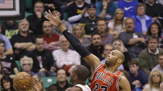 Utah Jazz's Paul Millsap, left, lays the ball as Chicago Bulls' Taj Gibson (22) defends during the first quarter of an NBA basketball game Friday, Feb. 8, 2013, in Salt Lake City. (AP Photo/Rick Bowmer)