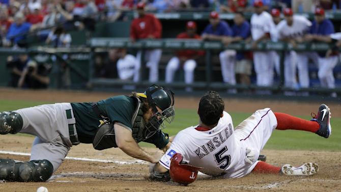 Oakland Athletics catcher John Jaso (5) is unable to hold on to the ball after a collision with Texas Rangers' Ian Kinsler, right, at the plate in the third inning of a baseball game Tuesday, June 18, 2013, in Arlington, Texas. Kinsler was safe at the plate on a A.J. Pierzynski single. (AP Photo/Tony Gutierrez)
