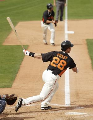 San Francisco Giants' Buster Posey hits a two-run double off Seattle Mariners starting pitcher Blake Beavan during the sixth inning of their spring training baseball game in Scottsdale, Ariz., Sunday, March 6, 2011. Giants' Andres Torres, background, looks on. San Francisco won the game 6-1. (AP Photo/Eric Risberg)