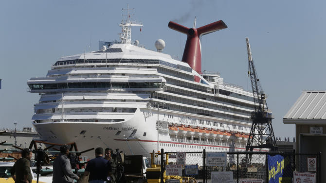 The cruise ship Carnival Triumph is moored at a dock in Mobile, Ala., Friday, Feb. 15, 2013. The ship, which docked Thursday in Mobile after drifting nearly powerless in the Gulf of Mexico for five days, was moved Friday from the cruise terminal to a repair facility. The ship carrying more than 4,200 passengers and crew members had been idled for nearly a week in the Gulf of Mexico following an engine room fire. (AP Photo/Dave Martin)