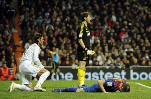 Real Madrid's goalkeeper and captain Iker Casillas (C) and Barcelona's midfielder Andres Iniesta (R) react
