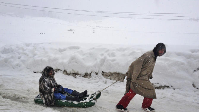 In this photo taken Tuesday, Feb. 26, 2013, a Kashmiri sledge puller pulls along an Indian tourist in Gulmarg, Kashmir. Gulmarg, a ski resort nestled in the Himalayan mountains in Indian-held Kashmir is one of the most militarized places on earth. (AP Photo/Kevin Frayer)