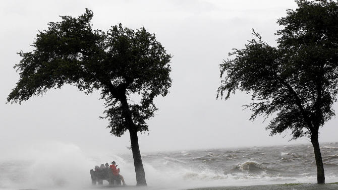 People sit on a bench along the seawall in the storm surge from Isaac, on Lakeshore Drive along Lake Pontchartrain, as the storm approaches landfall, in New Orleans, Tuesday, Aug. 28, 2012. (AP Photo/Gerald Herbert)