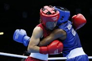 M.C. Mary Kom of India (in red) defends against Nicola Adams of Great Britain (in blue) during the women's Flyweight boxing semi-finals of the 2012 London Olympic Games at the ExCel Arena in London. India's five-time world champion M.C. Mary Kom apologised after being knocked out of the Olympic Games flyweight semi-finals