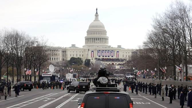 President Barack Obama and first lady Michelle Obama ride up Pennsylvania Avenue in the presidential motorcade towards the U.S. Capitol in Washington, Monday, Jan. 21, 2013, ahead of his ceremonial swearing in during the 57th Presidential Inauguration. (AP Photo/Charles Dharapak)