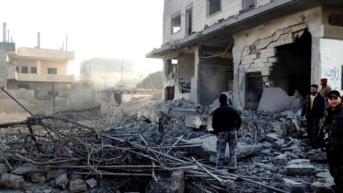 In this citizen journalism image provided by Edlib News Network, ENN, which has been authenticated based on its contents and other AP reporting, Syrian rebels stand in the rubble of damaged buildings due to government airstrikes, in Bensh, Idlib Province, northern Syria, Tuesday, Jan. 15, 2013. (AP Photo/Edlib News Network ENN)