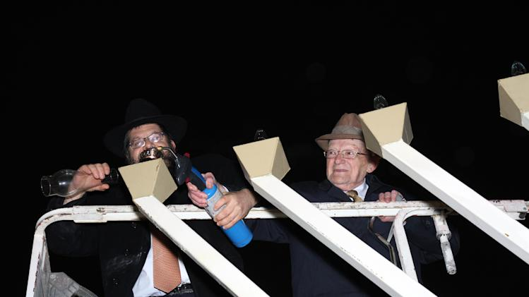 "Rabbi Areyah Kaltmann of the Lori Schottenstein Chabad Center in New Albany, prepares to light the menorah with the help Holocaust survivor, Abe Weinrib, Saturday, Dec. 8, 2012 in Columbus, Ohio. The start of Hanukkah on Saturday night had special meaning for Weinrib, a Holocaust survivor in Ohio who turns 100 next week. As a victim of the Holocaust, ""it's a miracle I survived,"" Weinrib, who will turn 100 on Tuesday. (AP Photo/Lori Schottenstein Chabad Center, Laurence Gilbert)"