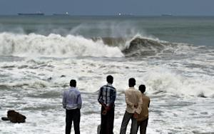 Indian youths stand on the shore as high tidal waves …