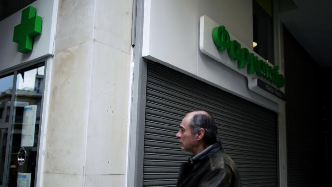 A man walks past a shuttered central Athens chemists' shop during a 24-hour strike by pharmacists Tuesday, Dec. 11, 2012. Greece was expected to announce later Tuesday the results of a bond buyback hoped to cut some 20 billion euros off the country's 340 billion euro debt load. Domestic lenders will  contribute strongly in the European-funded buyback, which if successful will open the way for disbursement of a delayed international rescue loan payment. (AP Photo/Petros Giannakouris)