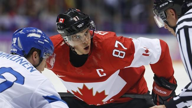 Canada forward Sidney Crosby watches the official during a face-off against Finland forward Jarkko Immonen in the first period of a men's ice hockey game at the 2014 Winter Olympics, Sunday, Feb. 16, 2014, in Sochi, Russia. (AP Photo/Mark Humphrey)