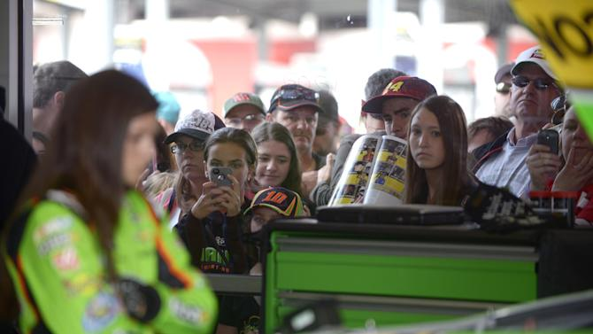Fans per through a window of the garage of Danica Patrick, left, taking photos and holding up programs hoping to get an autograph from the driver during practice for the NASCAR Daytona 500 Sprint Cup Series auto race at Daytona International Speedway, Saturday, Feb. 16, 2013, in Daytona Beach, Fla. (AP Photo/Phelan M. Ebenhack)