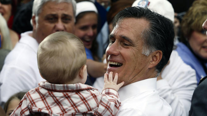 Republican presidential candidate and former Massachusetts Gov. Mitt Romney picks up a baby as he campaigns in front of The Golden Lamb Inn and Restaurant in Lebanon, Ohio, Saturday, Oct. 13, 2012. (AP Photo/Charles Dharapak)