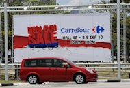 A motorist drives past an advertisement for Carrefour in Singapore. Carrefour said on Tuesday that it was pulling out of Singapore with the closure of its two existing outlets in the city-state by the end of this year