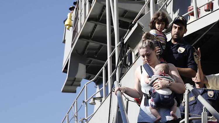 A woman evacuated from Libya carries her baby upon arrival at a port of Piraeus, near Athens, Greece, on Saturday, Aug. 2, 2014. A Greek navy frigate carrying embassy staff and nearly 200 people from Greece, China and other countries evacuated from the conflict in Libya returned early Saturday to the port. The Greek Defense Ministry the ship transported 77 people from Greece, 78 from China, 10 from Britain, seven from Belgium, one each from Russia and Albania. (AP Photo/Petros Giannakouris)