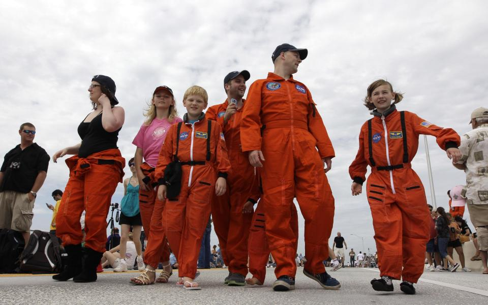 The Howard family from Huddersfield, England, walk along the Max Brewer Bridge before the launch of space shuttle Atlantis Friday, July 8, 2011, in Titusville, Fla. Atlantis is scheduled to liftoff Friday on the final space shuttle mission. (AP Photo/David J. Phillip)