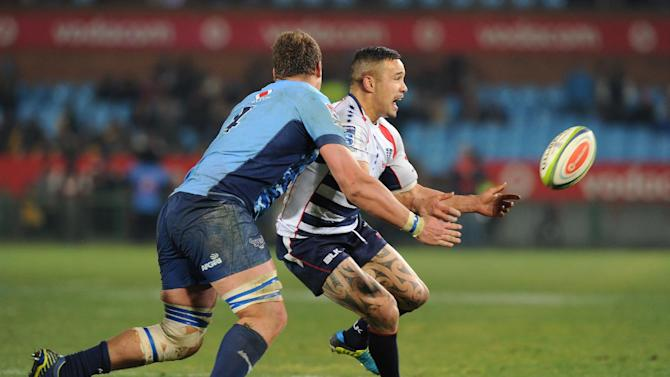 Tamati Ellison(R) of Rebels clears the ball with Paul Willemse(L) of Bule Bulls during their Super Rugby match on July 11, 2014 in Pretoria, South Africa