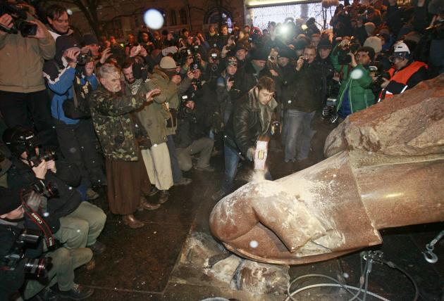 People surround a statue of Soviet state founder Vladimir Lenin, which was toppled by protesters, during a rally organized by supporters of EU integration in Kiev