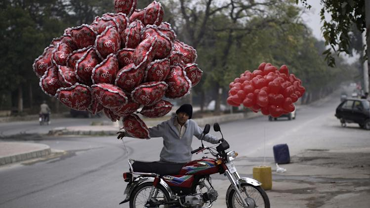 A Pakistani youth pushes his motorcycle, with balloons that he hopes to sell on Valentine's Day, in Islamabad, Pakistan, Thursday, Feb. 14, 2013. Romance may not be dead in Pakistan but it is under attack. Conservatives in Pakistan are attacking the romantic holiday as a western-inspired event helping to spread vulgarity in their country and putting up posters calling on people to boycott the holiday. But romantics are fighting back with an arsenal of flowers, pink teddy bears and heart-shaped balloons. (AP Photo/Muhammed Muheisen)
