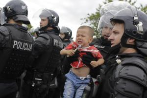 A Slovenian police holds a crying child after it was…