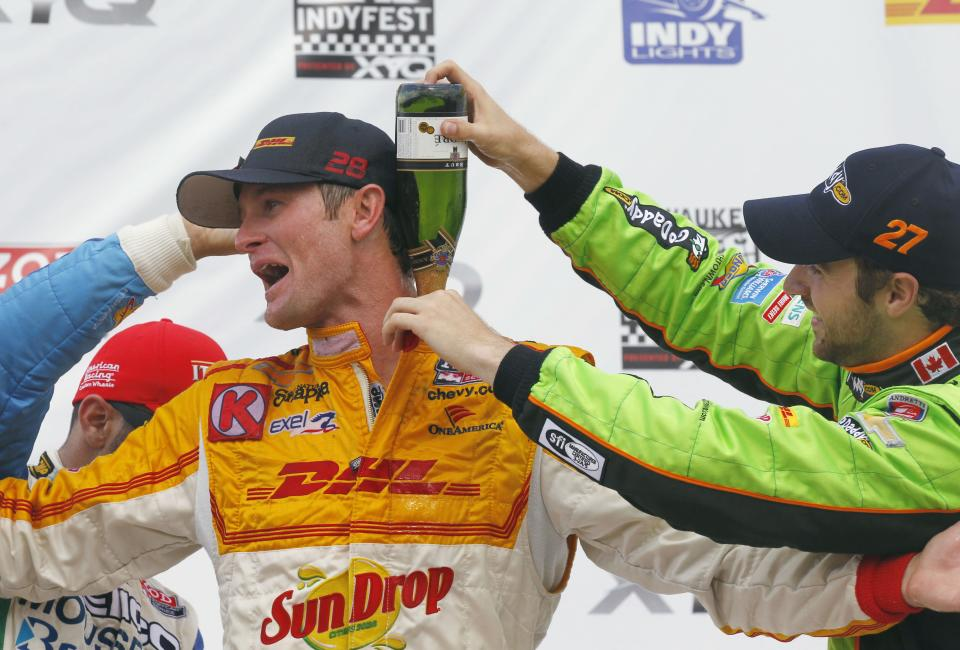 Third-place finisher James Hinchliffe, right, and second-place Tony Kanaan, left, pour champagne down the back of winner Ryan Hunter-Reay after the IndyCar auto race at the Milwaukee Mile in West Allis, Wis., Saturday, June 16, 2012. (AP Photo/Jeffrey Phelps)