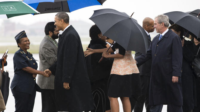 U.S. President Barack Obama, left, first lady Michelle Obama, under umbrella, and former President George W. Bush are greeted as they arrive at Waterkloof Air Base for a memorial service in honor of former South African leader Nelson Mandela on Tuesday, Dec. 10, 2013, in Centurion, South Africa. World leaders, celebrities, and citizens from all walks of life gathered for a memorial service on Tuesday to pay respects to Mandela. (AP Photo/ Evan Vucci)