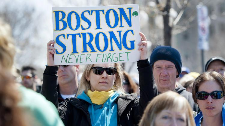 Ottawa runner Shelley Baran holds a sign in tribute to the victims of the Boston Marathon bombings, at the United States Embassy in Ottawa after marching in solidarity with the Boston community on Monday, April 22, 2013. (AP Photo/The Canadian Press, Justin Tang)