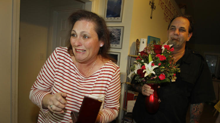 "IMAGE DISTRIBUTED FOR TELEFLORA - Kim Draluck, left, reacts to winning a stunning diamond necklace valued at $15,000 in conjunction with Teleflora's Love Rocks Sweepstakes and receiving the Romantic Heartstrings Bouquet as her husband Doug looks on in Burlington, N.C., Wednesday, Jan. 30, 2013. Teleflora's ""Love Rocks"" sweepstakes launched on January 21 and runs until 10 p.m. (PST) February 10.  During the span of the sweeps, each time a customer places an order for a romantic Heartstrings Bouquet from teleflora.com, they will be automatically entered to win one of nine heart-shaped diamond necklaces valued at $15,000. Teleflora will select three lucky winners of a show-stopping diamond necklace every week leading up to Valentine's Day.  Get your orders in by Sunday night for the weekly Monday drawings starting January 28 with additional drawings on February 4 and February 11.  Orders placed early increase the odds of winning the lottery. (Jim R. Bounds/AP Images for Teleflora)"