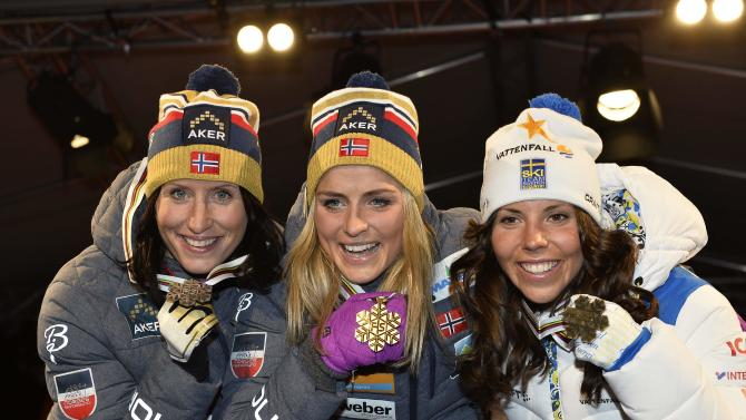 Medallists pose on the podium after their women's 30km mass start event at the FIS Nordic Skiing World Championships in Falun