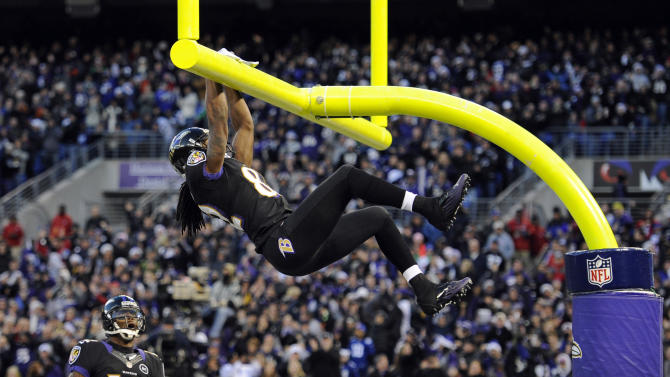 Baltimore Ravens wide receiver Torrey Smith, top, hangs from the goalpost after scoring a touchdown in the first half of an NFL football game against the New York Giants in Baltimore, Sunday, Dec. 23, 2012. (AP Photo/Nick Wass)