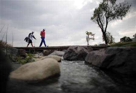 Luke Guthrie of U.S. walks to the ninth hole during the BMW Masters 2013 golf tournament in Shanghai