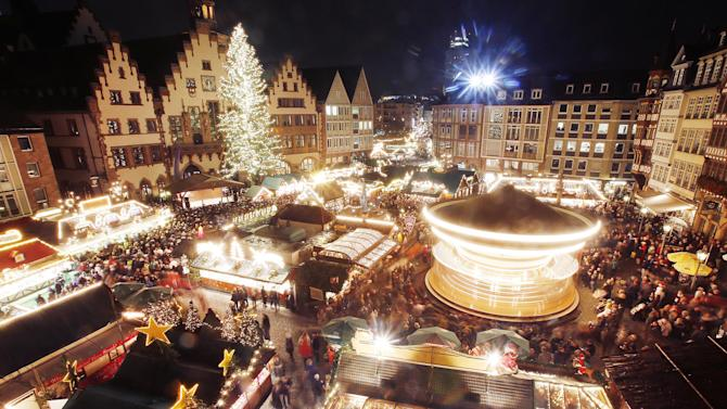 Hundreds of people gather to attend the opening of the traditional Christmas Market on the Roemerberg square in Frankfurt, Germany, Wednesday, Nov. 26, 2014. (AP Photo/Michael Probst)