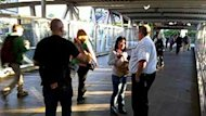 Transit security officers check passengers tickets at the Broadway SkyTrain station in Vancouver on Tuesday morning.