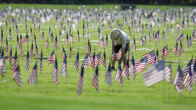 A man uprights a fallen flag at graves of military personnel and their families before Memorial Day ceremonies at Brig. General William C. Doyle Veterans Memorial Cemetery in Wrightstown N.J., Saturday, May 26,  2012. (AP Photo/MelEvans)