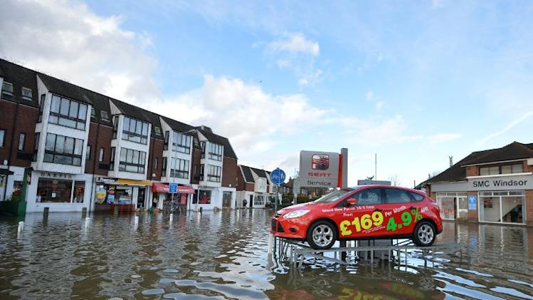 A display car at a car dealership sits on a ramp above floodwater in Datchet in Berkshire, southeast England, on February 10, 2014