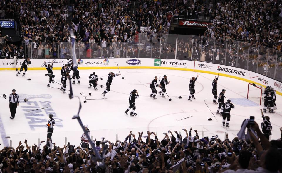 The Los Angeles Kings pour onto the ice to celebrate winning the Stanley Cup against the New Jersey Devils in Game 6 of the NHL hockey Stanley Cup finals, Monday, June 11, 2012, in Los Angeles. (AP Photo/Jae C. Hong)