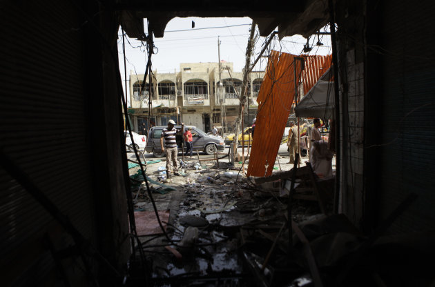 Iraqis inspect the aftermath of a late-night car bombing Monday near a cafe in al-Amin Shiite neighborhood in eastern Baghdad, Iraq, Tuesday, July 24, 2012. Violence shook more than a dozen Iraqi cities Monday, killing more than 100 people in coordinated bombings and shootings and wounding twice as many in the country's deadliest day in more than two years. (AP Photo/Khalid Mohammed)