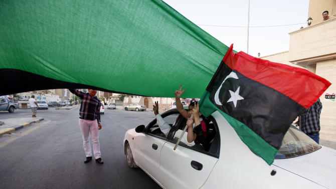 A Libyan girl waves the former Libyan flag from a car driving under agiant flag in the street of Jamal Goubtan district inTripoli, Libya, Thursday, Sept. 1, 2011. A TV station is quoting Moammar Gadhafi as warning that tribes loyal to him in key strongholds are armed and won't surrender to Libyan rebels. Thursday's report on Syrian-based Al-Rai TV comes as the rebels who have seized control of most of the country extended by a week a deadline for the surrender of Gadhafi's hometown of Sirte - originally set for Saturday.(AP Photo/Abdel Magid Al Fergany)