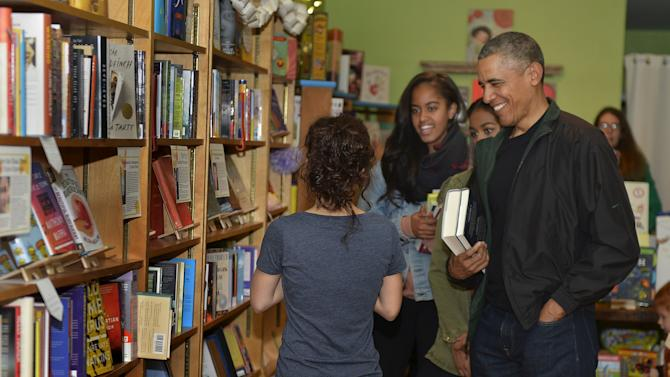 U.S. President Barack Obama and his daughters Malia and Sasha interact with Upshur Street Books manager Anna Thorn as they buy books from the store in Washington