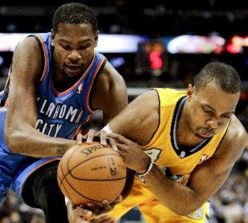 Oklahoma City Thunder's Kevin Durant, left, and Denver Nuggets' Randy Foye, right, fight for a loose ball, resulting in a jump ball, during the fourth quarter of an NBA basketball game Tuesday