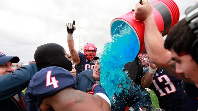 Arizona head football coach Rich Rodriguez is doused by his players after their 49-48 win over New Mexico in the New Mexico Bowl NCAA college football game in Albuquerque, N.M., Saturday, Dec. 15, 2012. (AP Photo/Eric Draper)