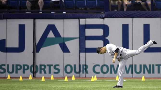 New York Yankees pitcher Masahiro Tanaka, of Japan, stretches in the outfield before a baseball game against the Tampa Bay Rays in St. Petersburg, Fla., Saturday, April 18, 2015.(AP Photo/Phelan M. Ebenhack)