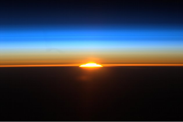 In this Sat., Aug. 27, 2011 photo provided by NASA and taken from aboard the international space station by astronaut Ron Garan, the sun rises above above the earth in one of the sixteen sunrises astr