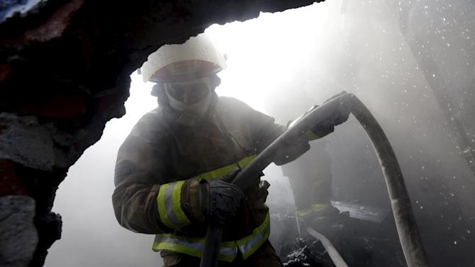 A firefighter works to extinguish a fire at a warehouse at the Grupo Modelo brewery in Mexico City