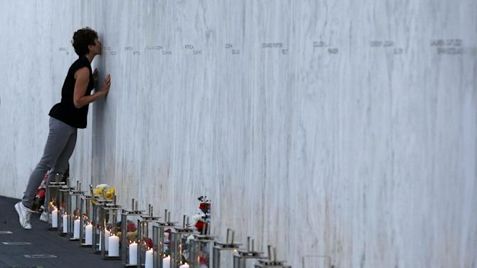A visitor kisses an name on the wall containing the 40 names of the crew and passengers of Flight 93 at the Flight 93 National Memorial during a candlelight remembrance on Tuesday, Sept. 10, 2013. (AP Photo/Gene J. Puskar)