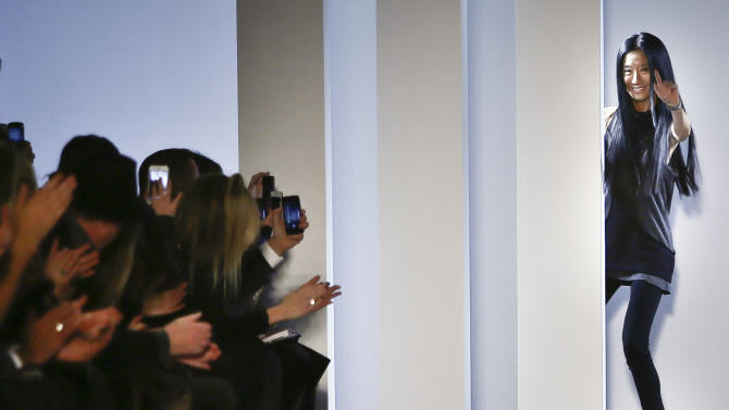 Fashion designer Vera Wang appears behind panels of a runway as she responds to applause following her Fall 2013 collection show on Tuesday, Feb. 12, 2013 in New York.  (AP Photo/Bebeto Matthews)