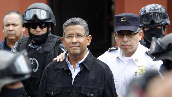 Former El Salvador President Flores walks out of his house while being guarded by Deputy Director of Police Cotto and the elite unit Reaction Police Group in San Benito