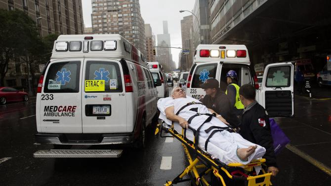 A patient is wheeled to an ambulance in the rain during an evacuation of New York University Tisch Medical, Tuesday, Oct. 30, 2012, in New York. Sandy, the storm which was downgraded from a hurricane just before making landfall, caused multiple fatalities, halted mass transit and cut power to more than 6 million homes and businesses (AP Photo/ John Minchillo)