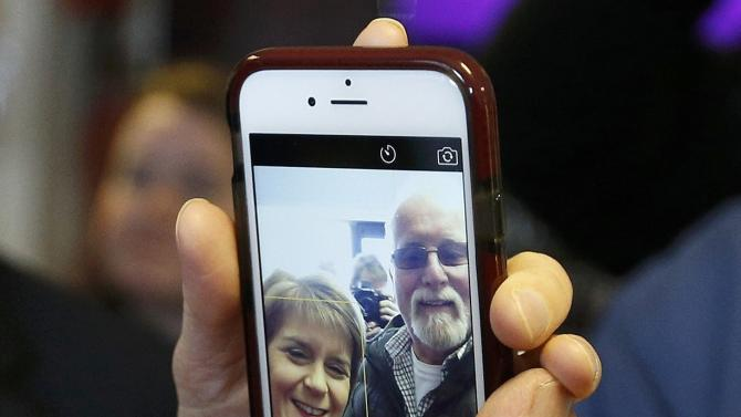 Supporters use their mobile phone to photograph Nicola Sturgeon, the leader of the Scottish National Party, as she visits the Cook School during a campaign event, in Kilmarnock, Scotland